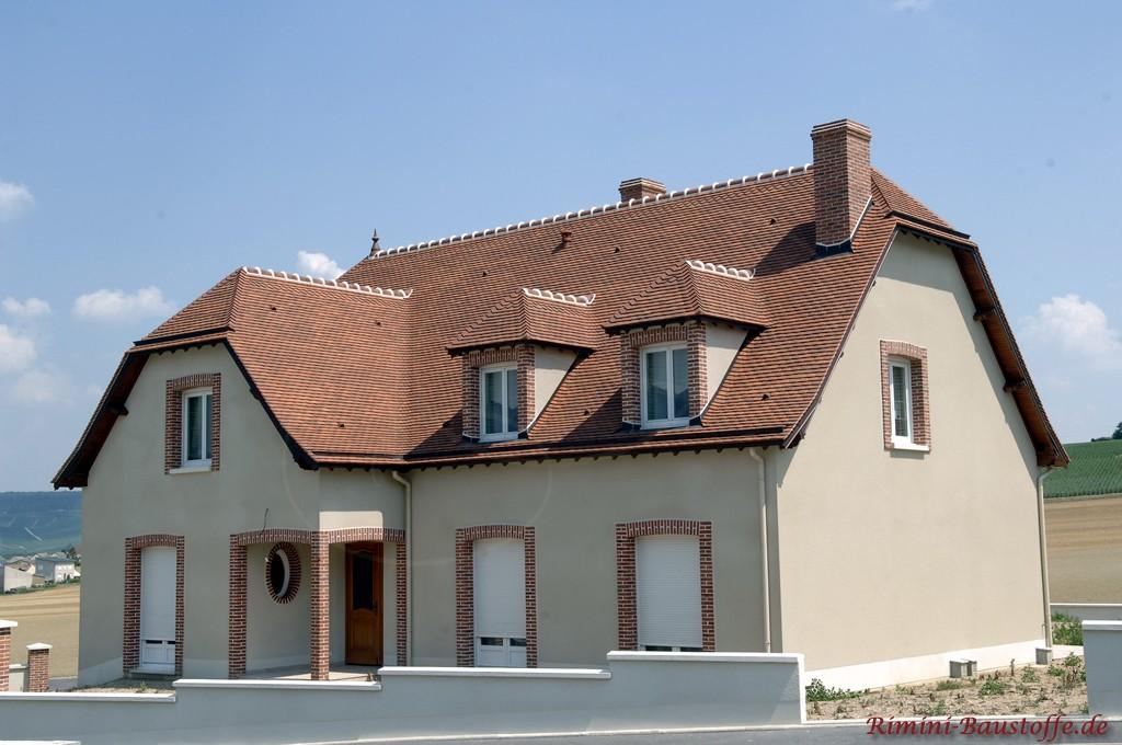Geputztes Einfamilienhaus mit Krüppelwalmdach das mit rötlichen Schindeln eingedeckt ist