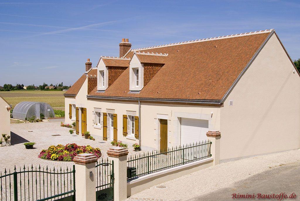 schönes Einfamilienhaus mit heller Putzfassade, holzfarbenen Fenstern und einer sehr schönen kräftigen mediterranen Dachfarbe