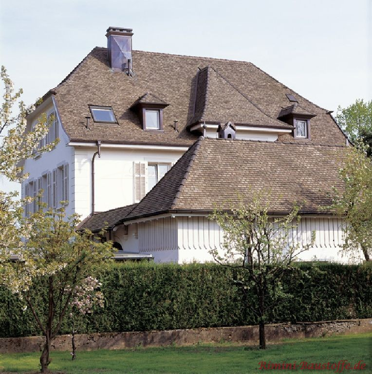 älteres Gebäude mit weißer Putzfassade und antik wirkenden Ziegeln in Braun