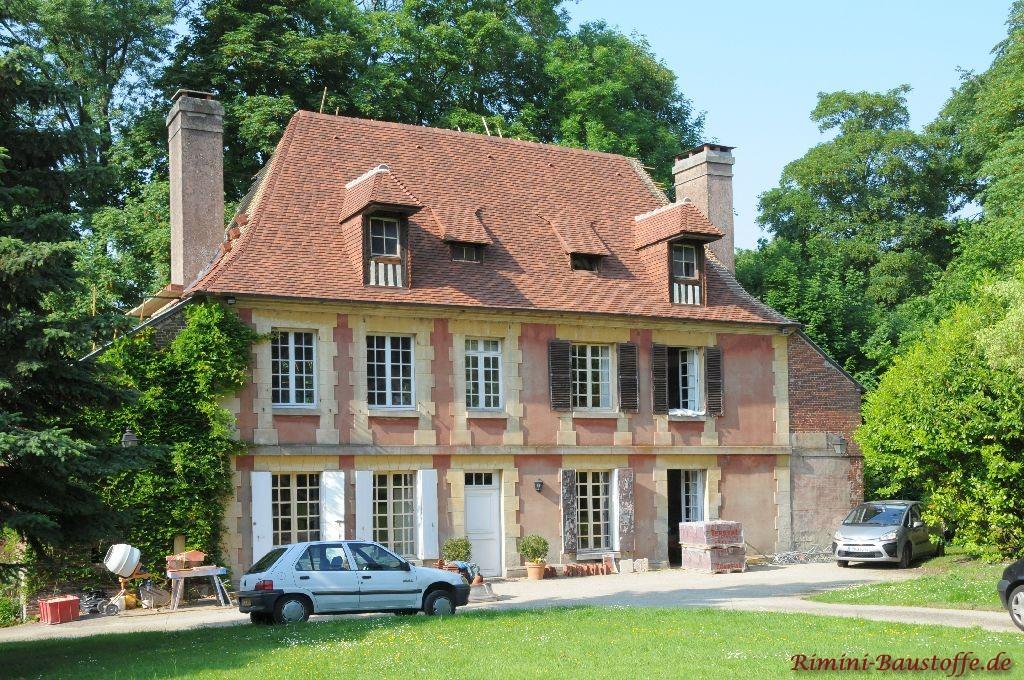 große mediterrane Villa mit vielen weißen Sprossenfenstern und einer sehr hohen Dachneigung