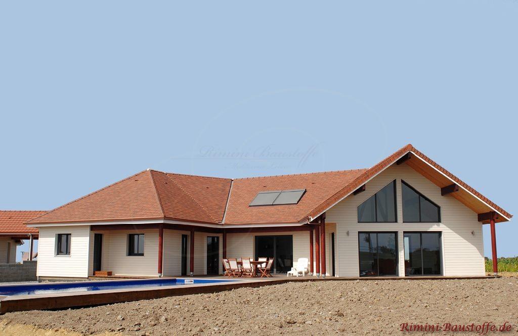 mediterrane Villa mit großer Fensterfront und einem sehr schönen Dach das im Kontrast zu der hellen Fassade steht