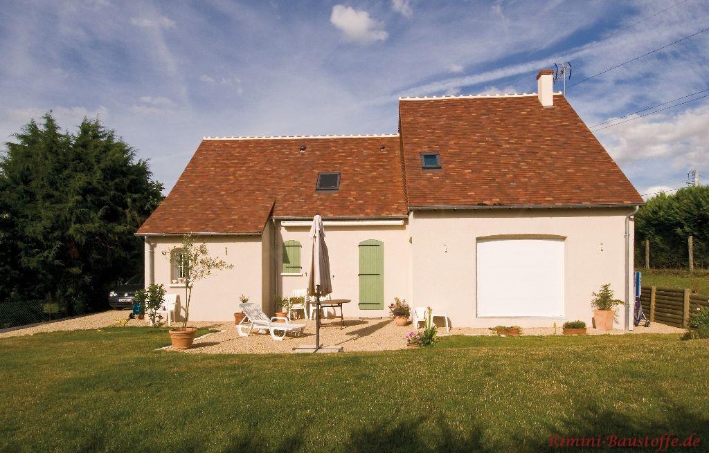 schönes Kleines Haus mit heller Putzfassade, grünen Fensterläden und einem kräftigen roten Dach im Kontrast