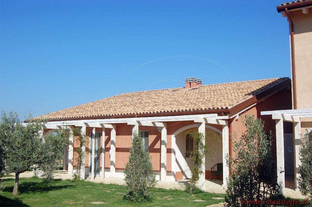 kleines Haus im südländischen Stil mit hautfarbener Fassade und weißen Pfeilern rund ums Haus