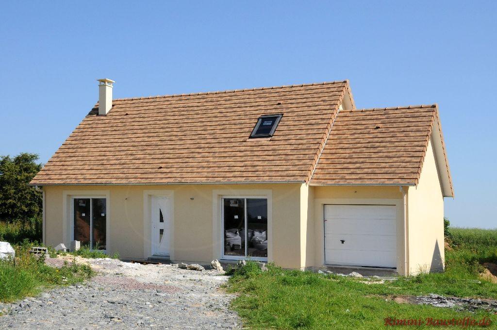 kleines Einfamilienhaus mit hellgelber Putzfassade, weißen Fenstern und einem hellen rötlichen Satteldach