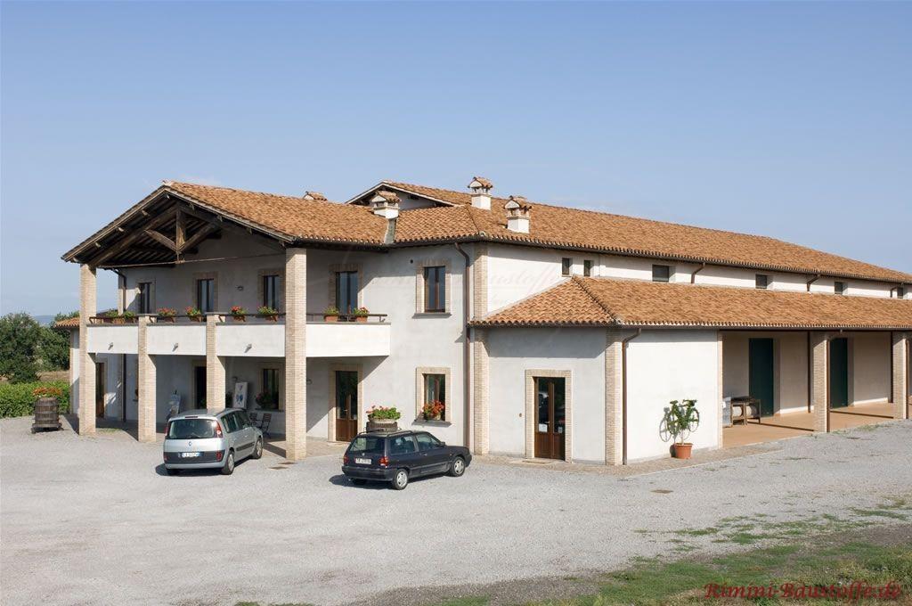 großes abgestimmtes Anwesen mit geller Putzfassade, Pfeilern im Eingangsbereich und einem sehr schönen farblich passendem Dach