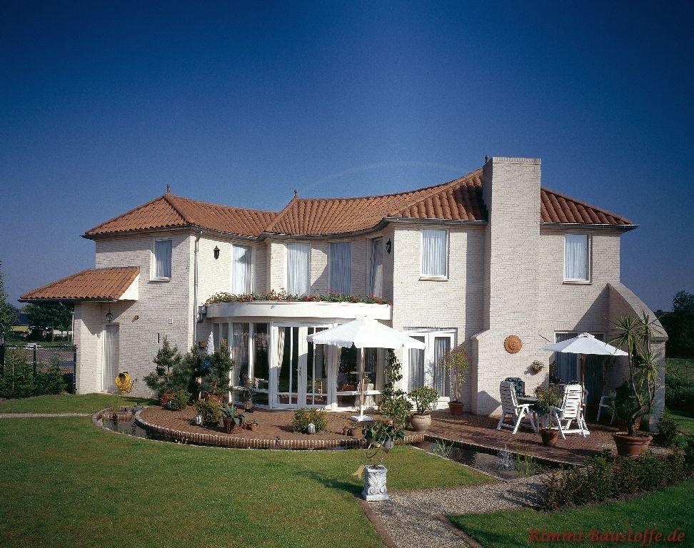 sehr schöne große Villa mit ausgefallener Archtektur und heller Putzfassade zu einem dunkelroten Dach mit mediterranen Dachziegeln