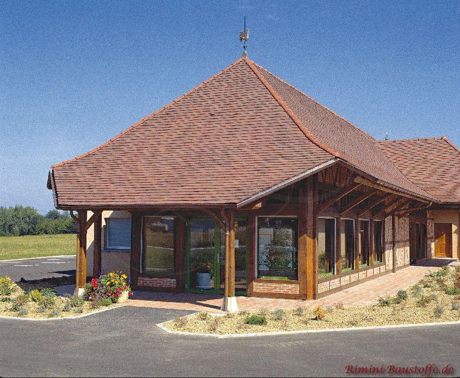 sehr schöne ausgefallene Architektur mir großen tiefen Fenstern in dunklem Holzton passend zur großen schönen Dachfläche