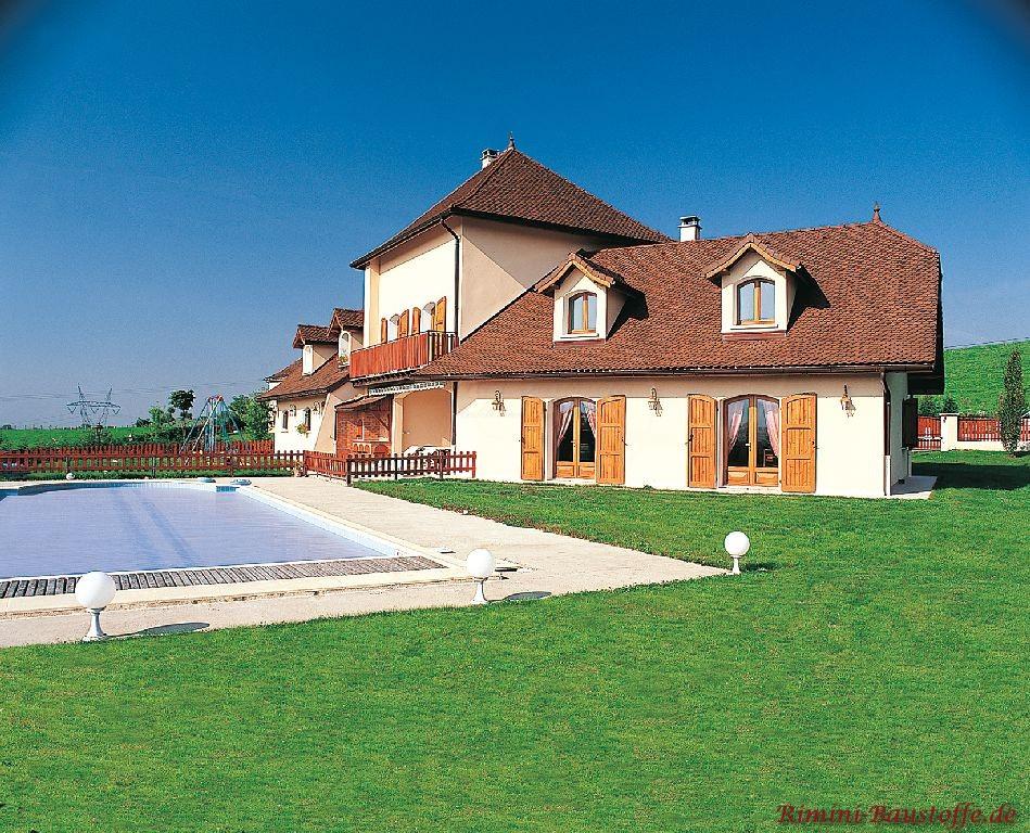 sehr schönes Einfamilienhaus im südländischen Stil mit weißen Fenstern und orangefarbener Putzfassade mit großem Garten und