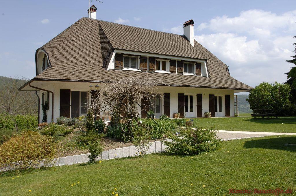 großes Wohnhaus mit schöner großer brauner Dachfläche und einem schönen großen Garten
