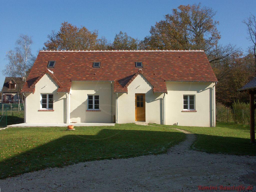 kleines antik wirkendes Wohnhaus ohne viele Verzierungen mit einer sehr schönen Dachfarbe auf dem Satteldach