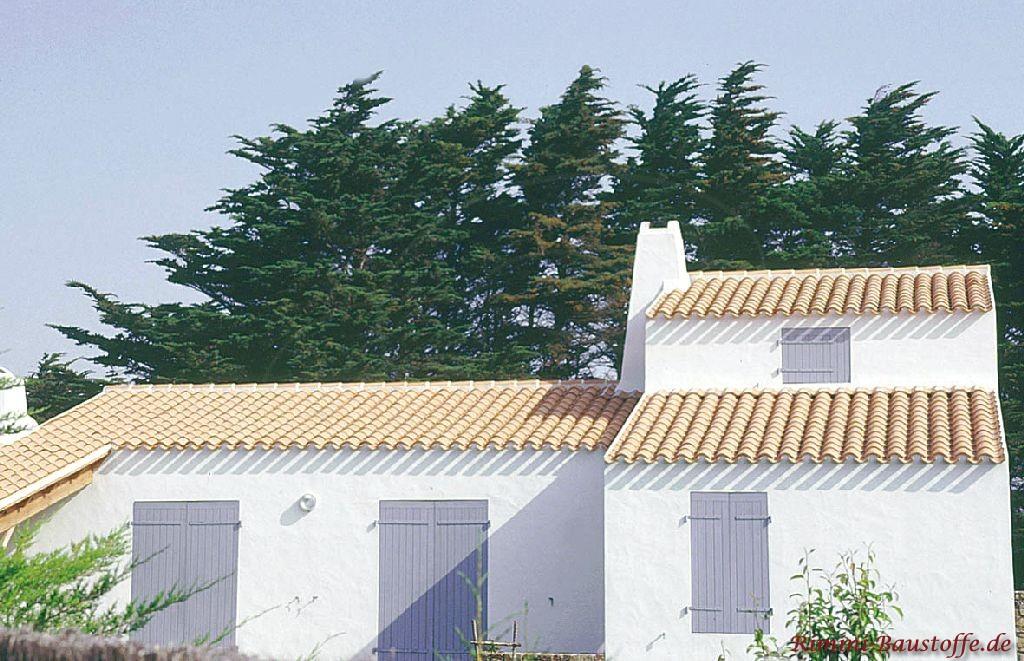 kleines Häuschen mit weißer Putzfassade, hellblauen Fensterläden und einer schönen milden Dachfläche