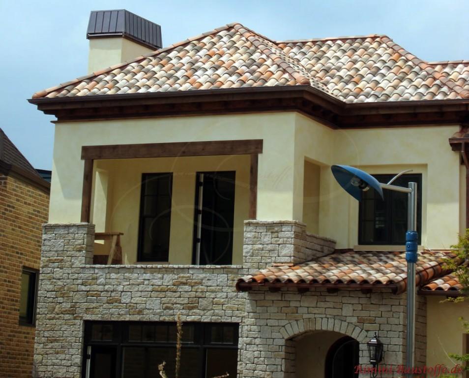 Einfamilienhaus mit hellgelber Putzfassade und halbhoher Natursteinoptik, dazu ein schönes mediterranes Dach
