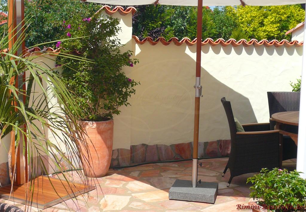 Schöne Terrasse im Sommer mit vielen Pflanzen und Sichtschutzmauer im mediterranem Stil