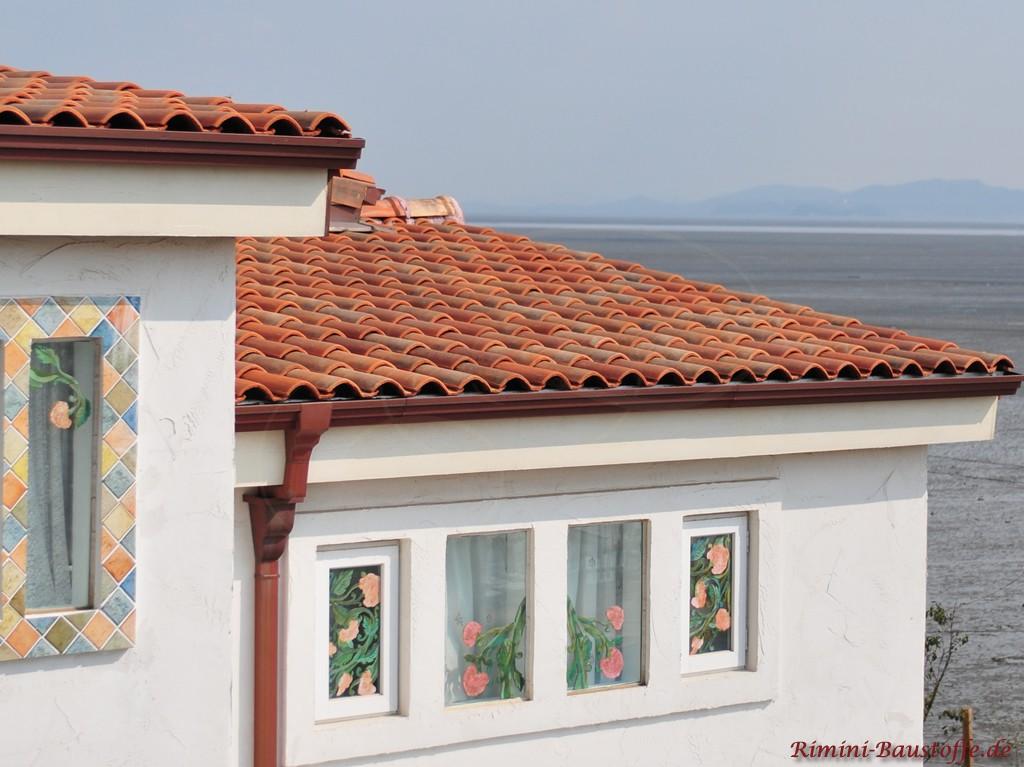 Haus nahe der Atlantikküste mit bunten Ziegeln und hellem Putz. Die Fenster sind bunt verziert