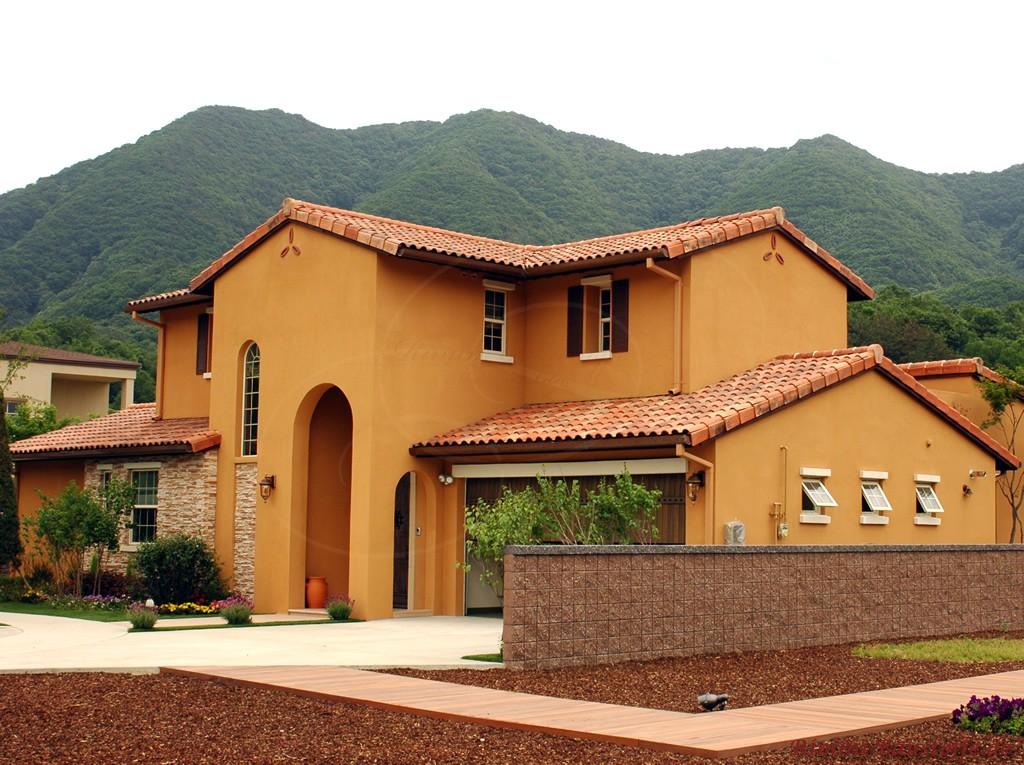 Orangefarbene Fassade mit rot geschecktem Dach. Das Haus hat einen sehr hohen Eingangsbereich