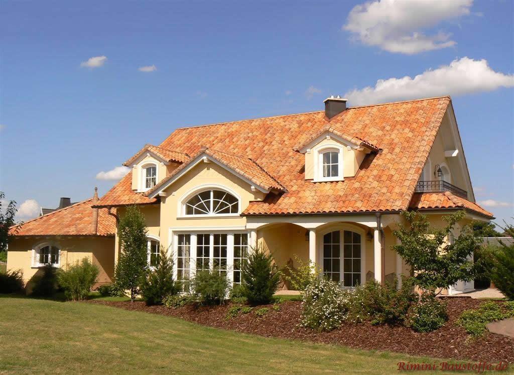 Mediterranes Einfamilienhaus mit Satteldach in warmen Farben. Auch der schönem Garten ist zu sehen