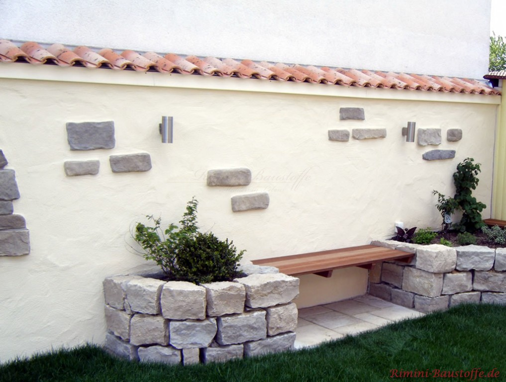 Sitzecke mit mediterranem Flair zwischen zwei Planzkübeln aus Sandstein. Im Hintergrund zu sehen ist eine Mauer wie im Süden