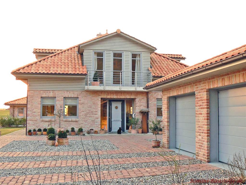 Auffahrt zu einem Haus mit Klinker und farbigem Dach, sowie grauem Garagentor