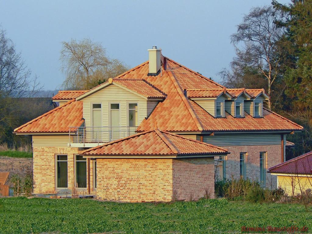 Kleines Klinkerhaus mit mediterranem Spitzdach und Geräteschuppen
