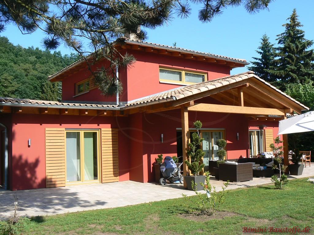 kräftige Rote Putzfassade mit holzfarbenen Fensterläden und einer schönen überdachten Terrasse