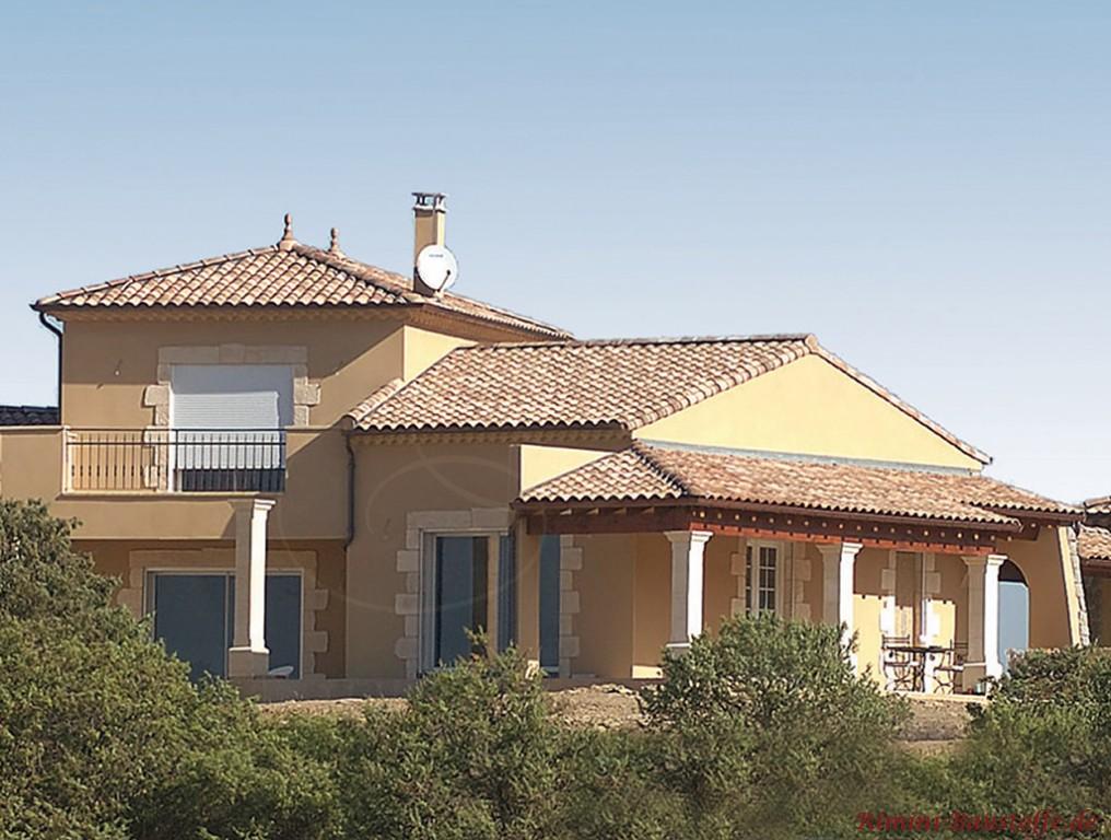 mediterrane Villa mit heller gelber Putzfassade und schöner farblich passender bräunlicher Dachfläche
