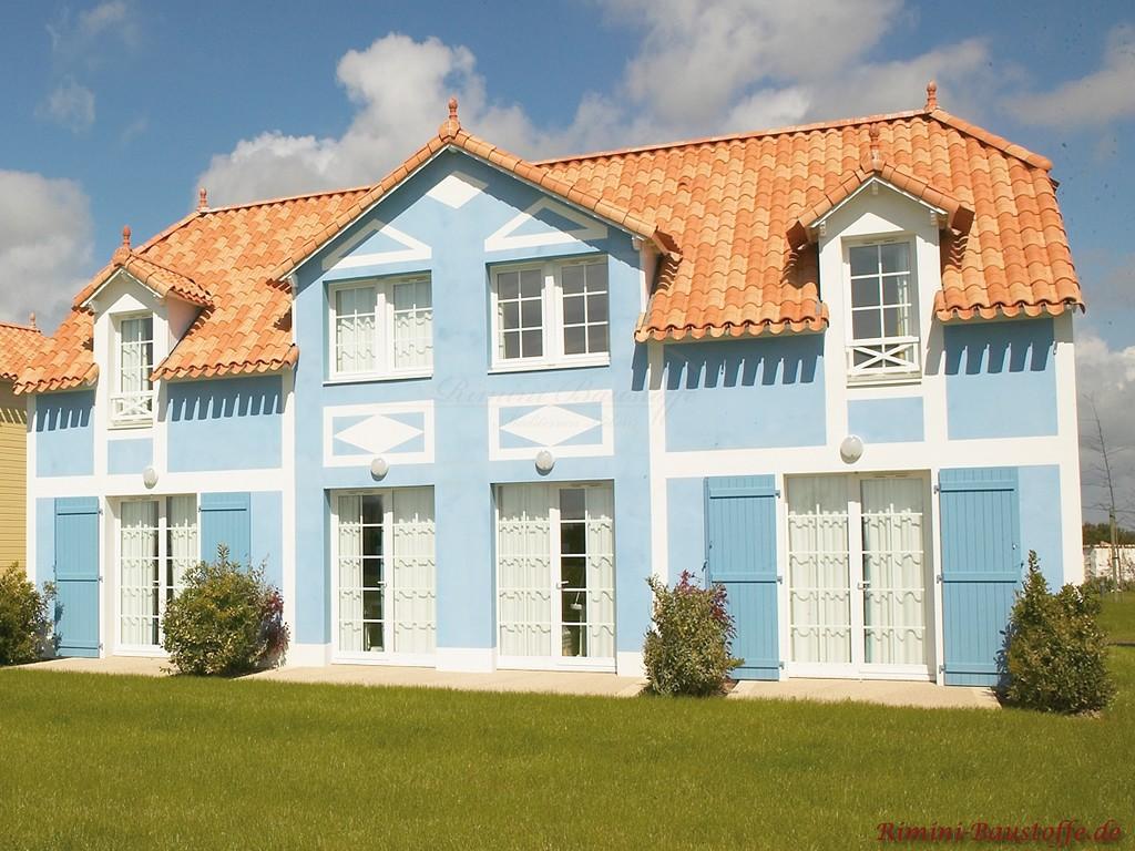 große Villa mit hellblauer Putzfassade und weißen Akzenten dazu passend ein schönes strahlend rotes Dach mit Gauben