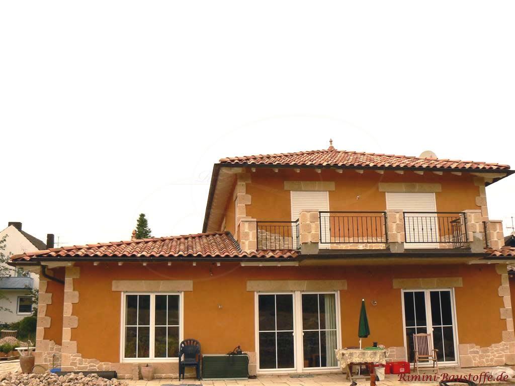 Einfamilienhaus im mediterranen Stil mit großen Fenstern und Natursteinoptikaccessoires