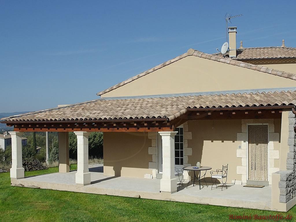 Dachüberstand über der Terrasse mit heller Putzfassade und passenden Dachziegeln