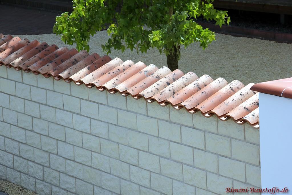 Lange Mauer die mit Riemchen verblendet wurde und mit mediterranen Ziegeln abgedeckt ist