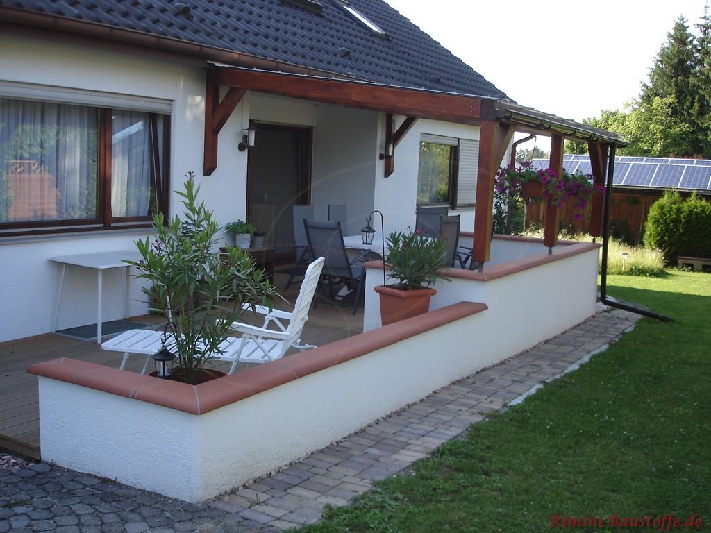 Mit einer niedrigen Mauer eingefasste Terrasse, die schön abgedeckt wurde um gegen Witterung zu schützen