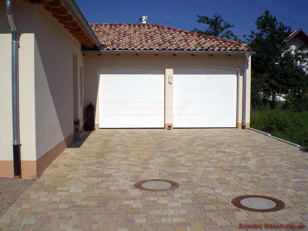 Garageneinfahrt von einem mediterranem Haus. Das Pflaster passt farblich sehr schön zum Dach