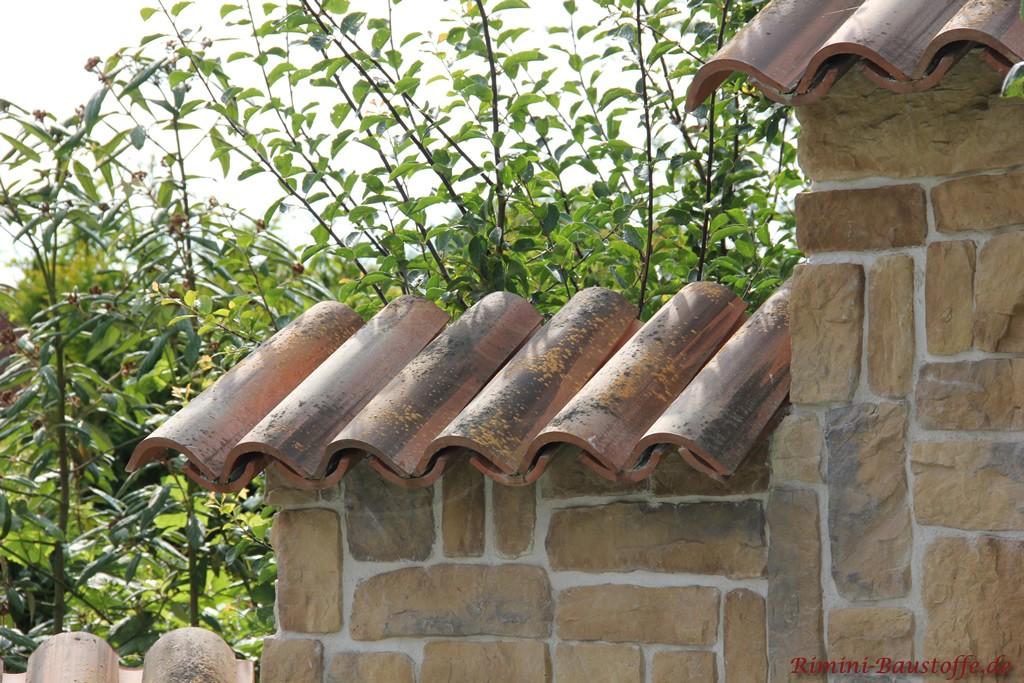 mediterrane Gartenmauer in Natursteinoptik und mit antiken Halbschalen gedeckt