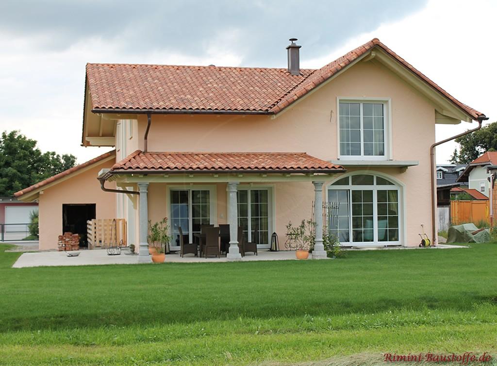 schönes großes Haus im mediterranen Stil mit hellgelber Putzfassade und passendem südländischen Ziegel