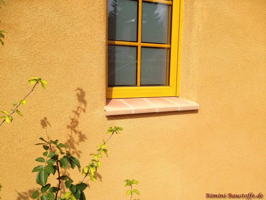 gelbe Putzfassade mit schoenen Fensterbaenken aus Ton