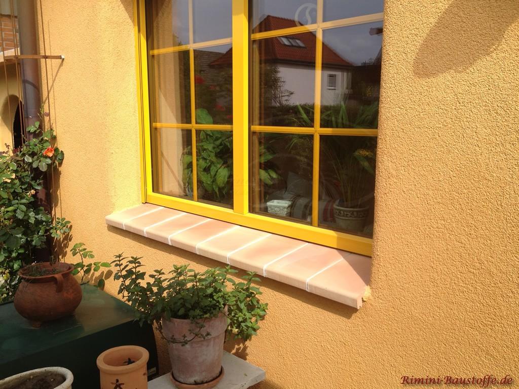 gelbe Fenster passend zur Fassade mit lachsfarbenen Fensterbaenken aus Ton