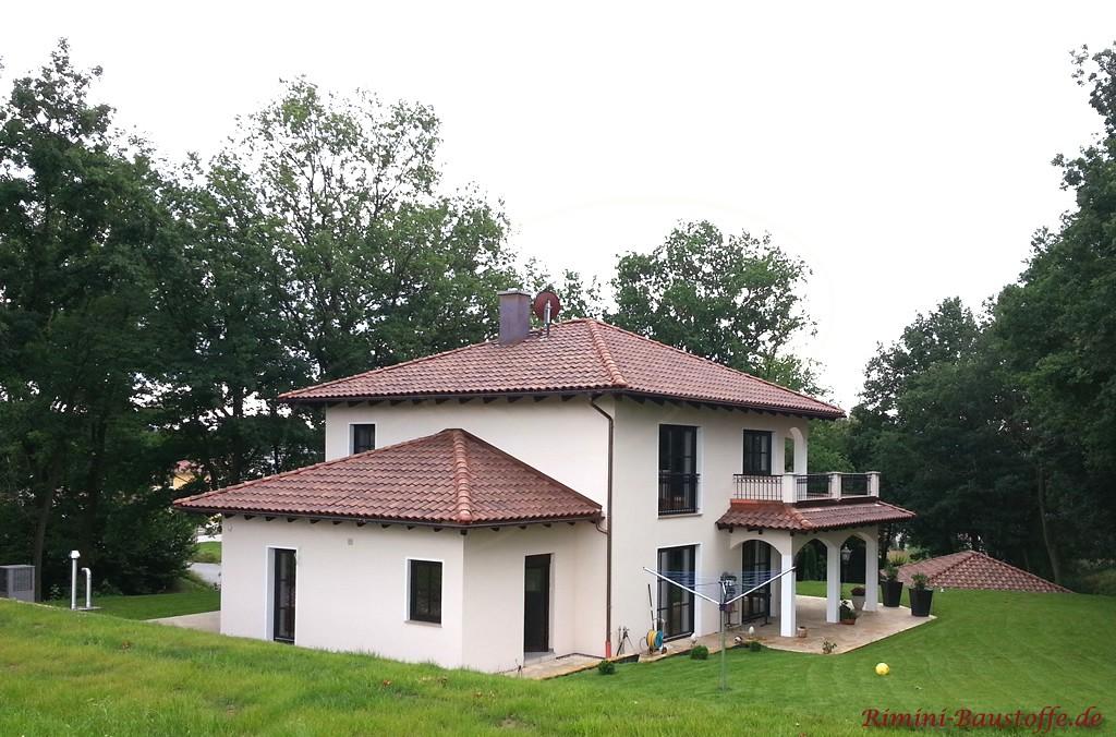 Toscanahaus mit sehr schöner hellen Putzfassade mit dunklen Holzfenstern und einem passenden Dach gedeckt mir romanischen Tondachziegeln
