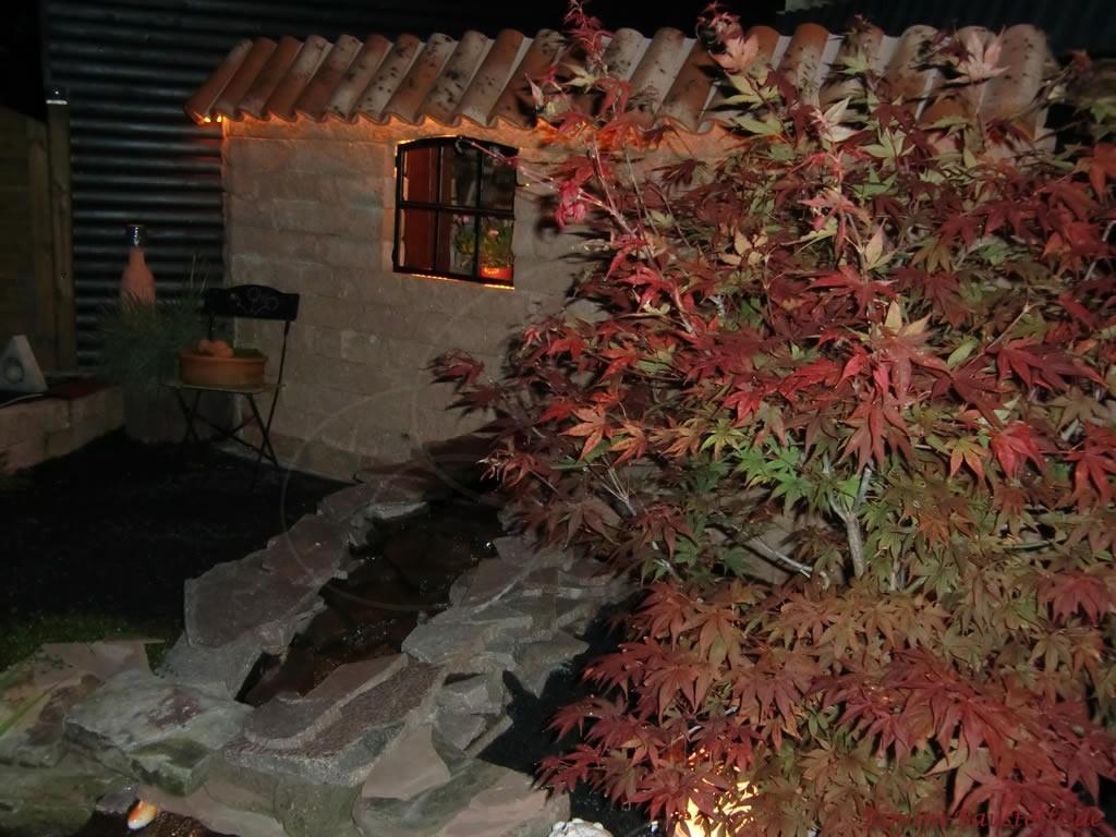 mediterrane Gartenmauer aus Naturstein im Dunkeln