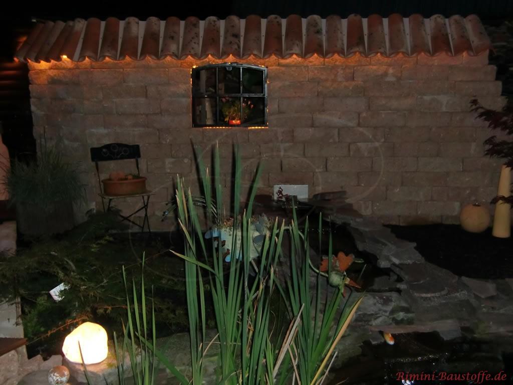 sehr schöne mediterrane Gartenmauer im Dunkeln beleuchtet an einem See