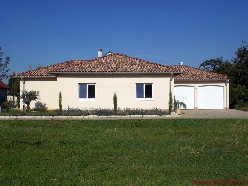 schöner Bungalow mit heller gelber Putzfassade und sehr schönem Dach in mediterranen Farben