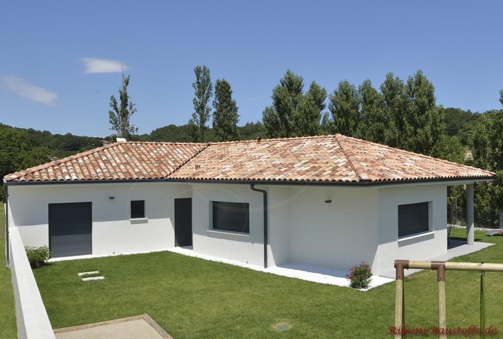 Bungalow mit weisser Putzfassade, Walmdach und schönem bunten Dachziegel