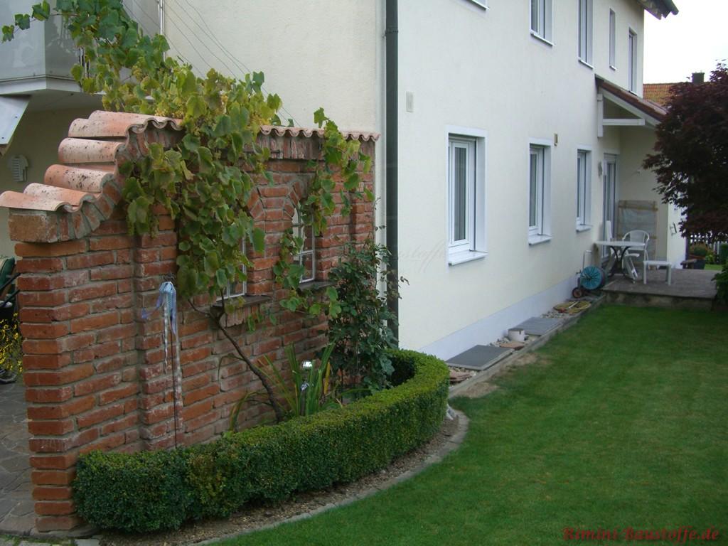schöne rustikale Gartenmauer mit kleinen Fenstern
