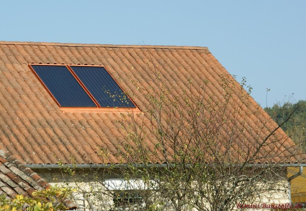 braunes Satteldach mit Solarzellen. Dachziegel mit Doppeloptik