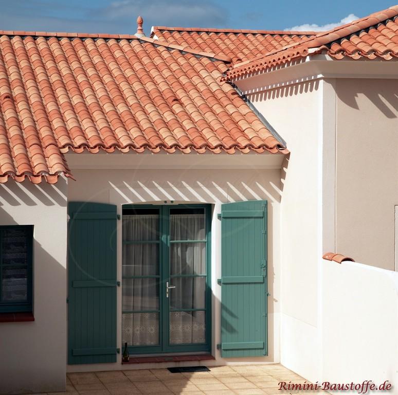 schöne grüne Fensterläden und helle Putzfassade im Kontrast zum kräftigen roten Dach