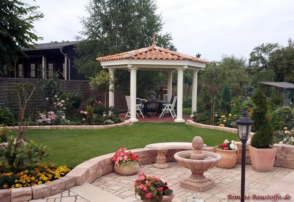 Garten im mediterranen Stil mit Sandsteinaccessoires und kleiner Laube