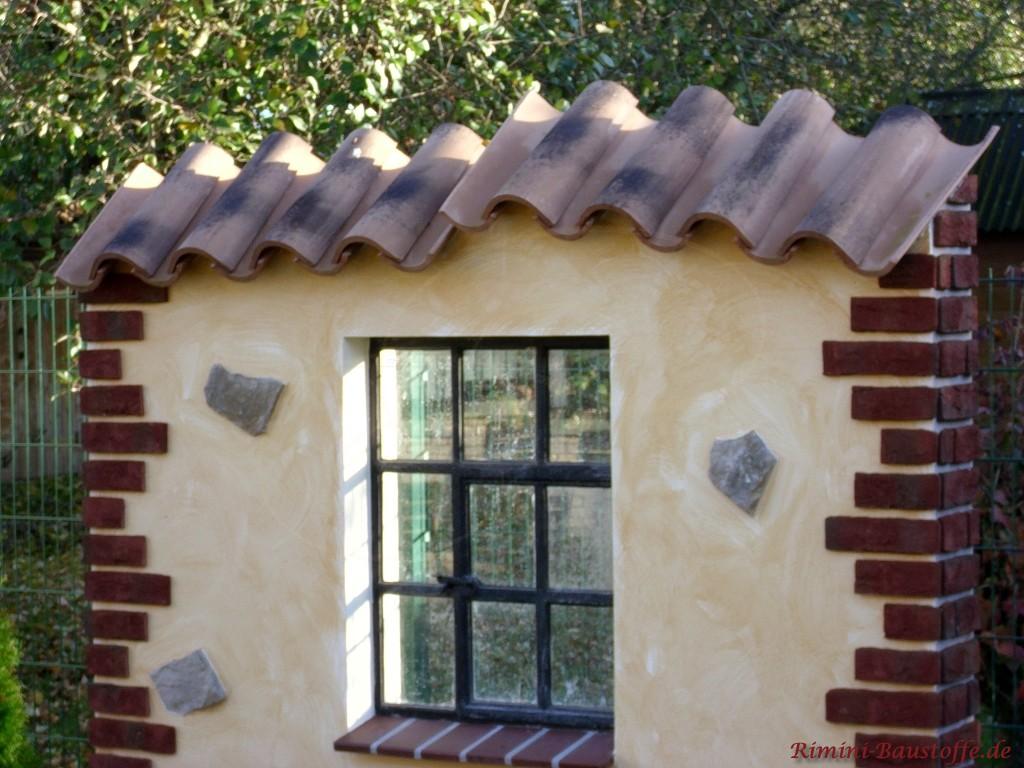 freistehende Gartenmauer mit Sprossenfenster und Bossen