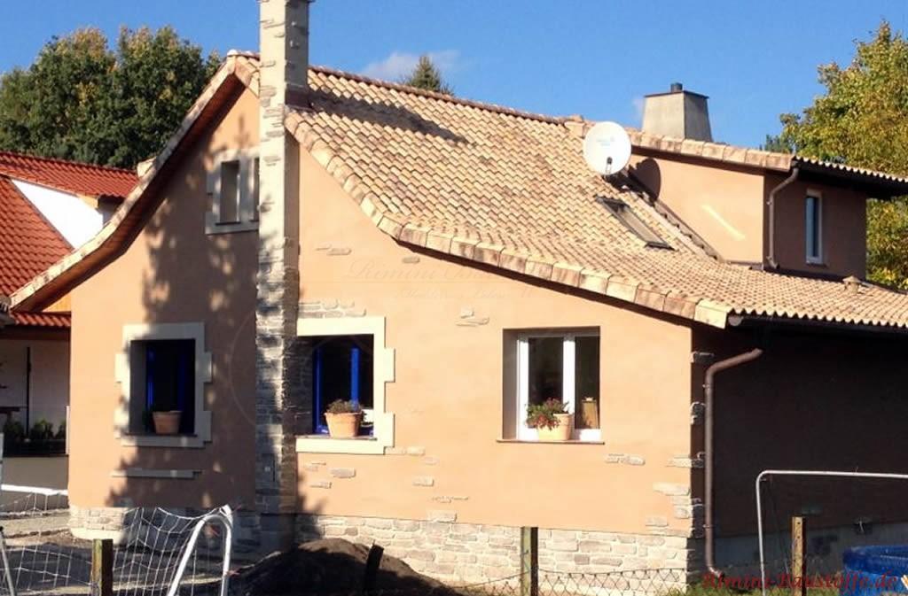 cappucinofarbene Putzfassade mit Natursteinelementen und einem passenden Dachziegel