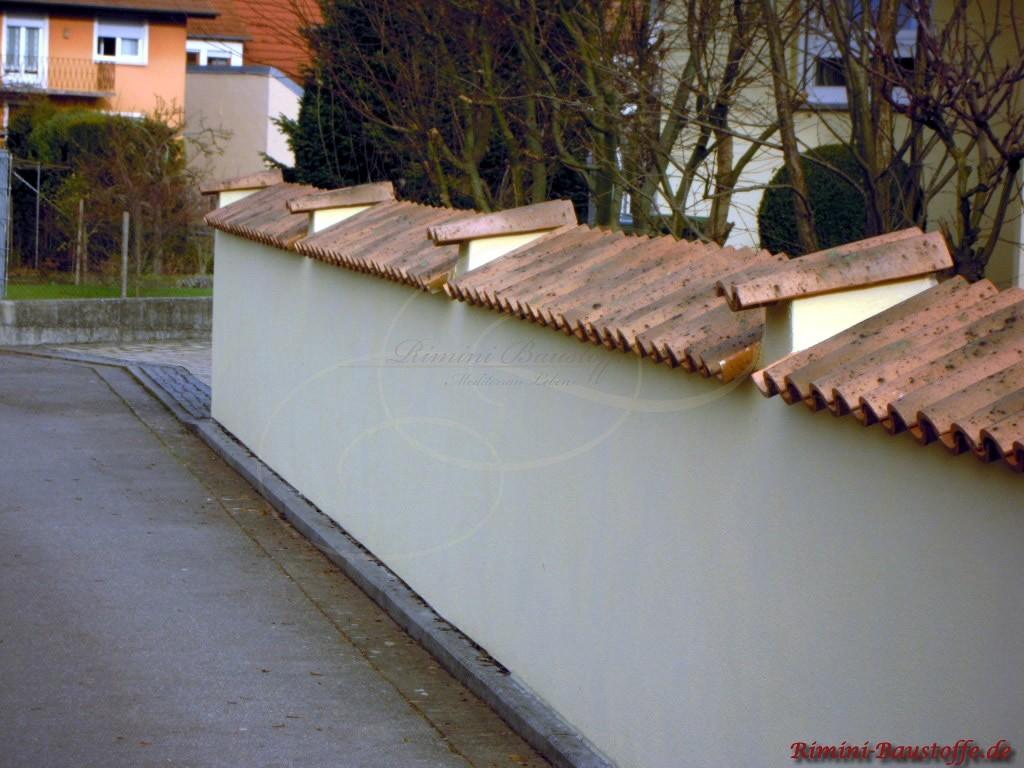 Helle Mauer die mit Tonziegeln abgedeckt ist. Es ragen drei Erhöhungen aus der Mauerkrone hervor