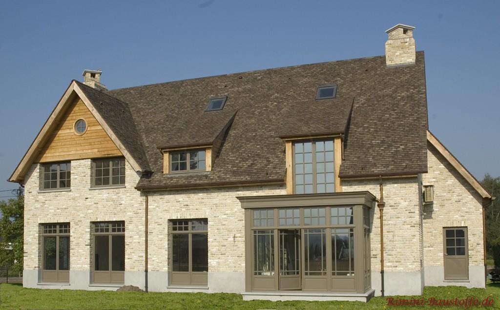 helle Klinkerfassade mit grauen Fenstern und farblich passenden Schindeln