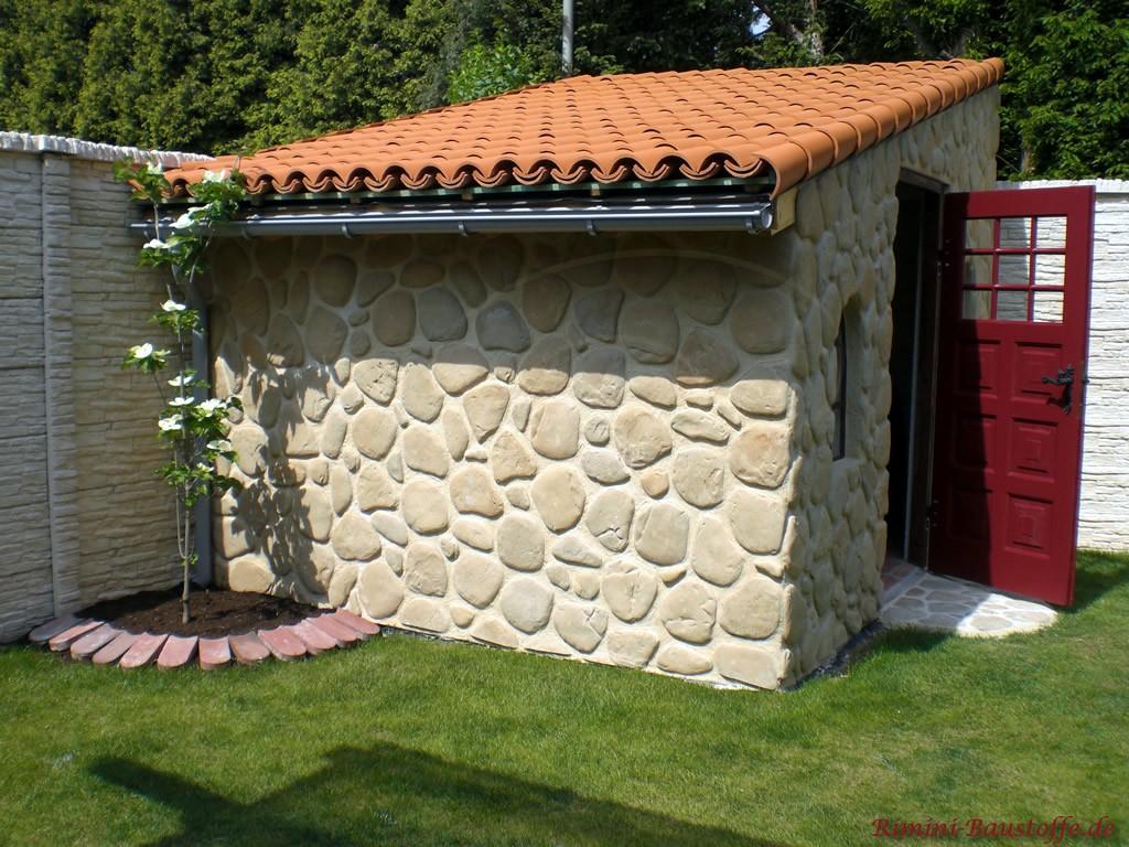 schönes Gartenhaus mit Flusssteinfassade und Halbschalen auf dem Dach