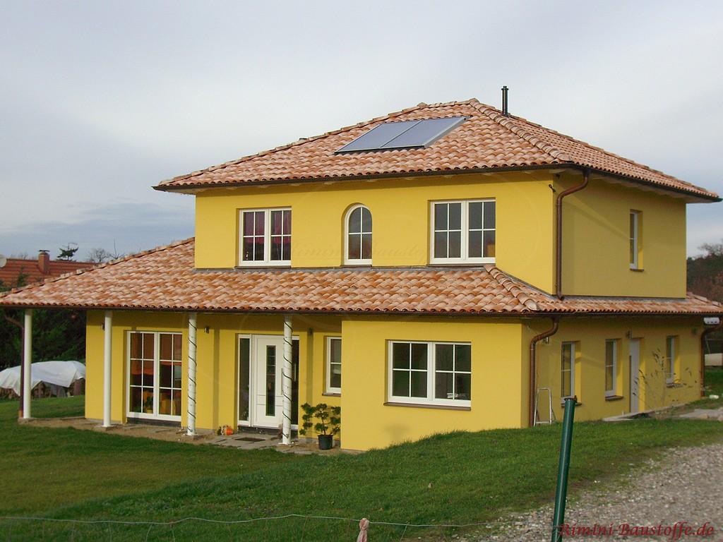 große mediterrane Villa mit kräftiger gelber Putzfassade